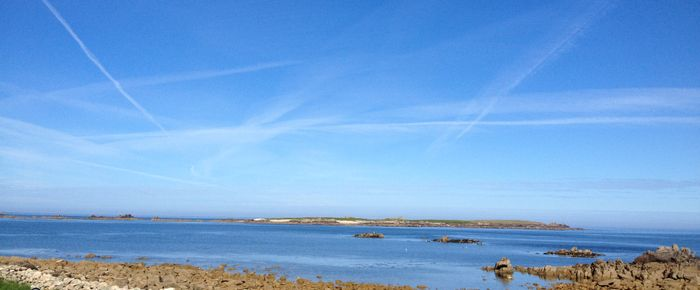 The Island of Annet in the Scillies on a clear day.   Vapour trails from aircraft leave their mark.